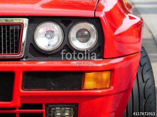 Doppelscheinwerfer im Kühlergrill einer knallroten italienischen Lancia Delta Integrale Sportlimousine mit breiten Kotflügeln in Wettenberg Krofdorf-Gleiberg