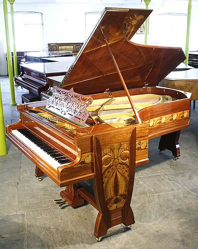 Bechstein Model C grand piano with a mahogany case inlaid with a variety of woods in an Art Nouveau design of flowers and tendrils at Besbrode Pianos. This piano had one previous owner Julius Gutermann, a wealthy victorian industrialist.