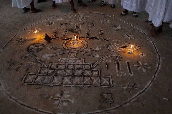 Candles burn within an image depicting a symbol dedicated to the Gede, a family of spirits that embody the power of death and fertility, during a Day of the Dead voodoo ritual in Petionville, a suburb of Port-au-Prince, Haiti