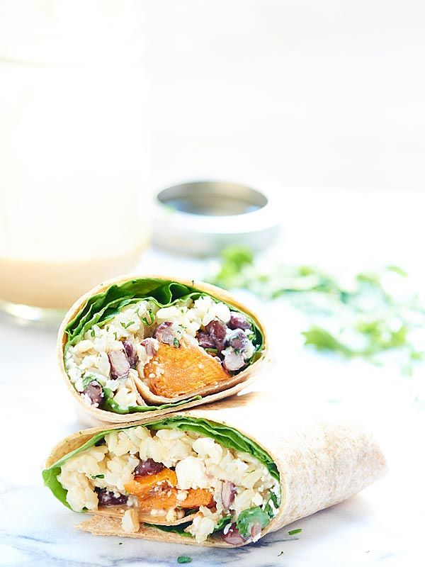 This healthy sweet potato wrap is hearty, vegetarian & full of good for you ingredients like black beans, brown rice & is drizzled in a unique tahini sauce! showmetheyummy.com #wrap #vegetarian