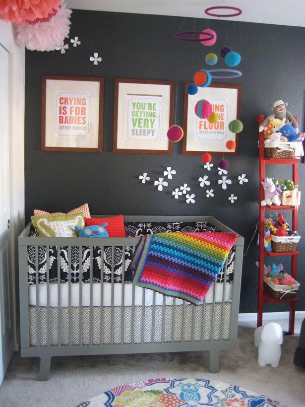 Quarto de bebê moderno com parede escura e berço cinza.
