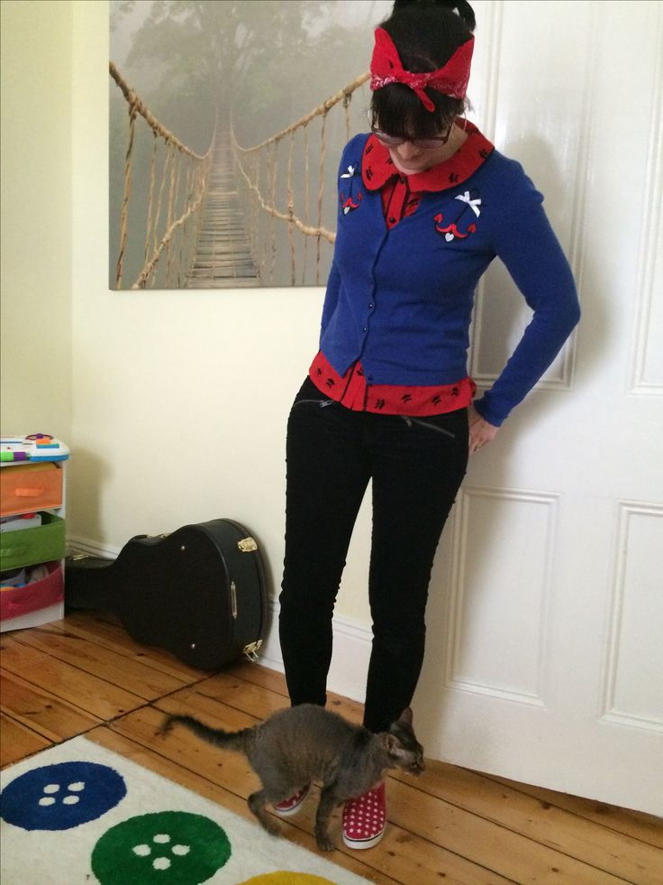 Black pants, red top with small print detail, royal blue cardigan with print detail, red shoes & bandanna
