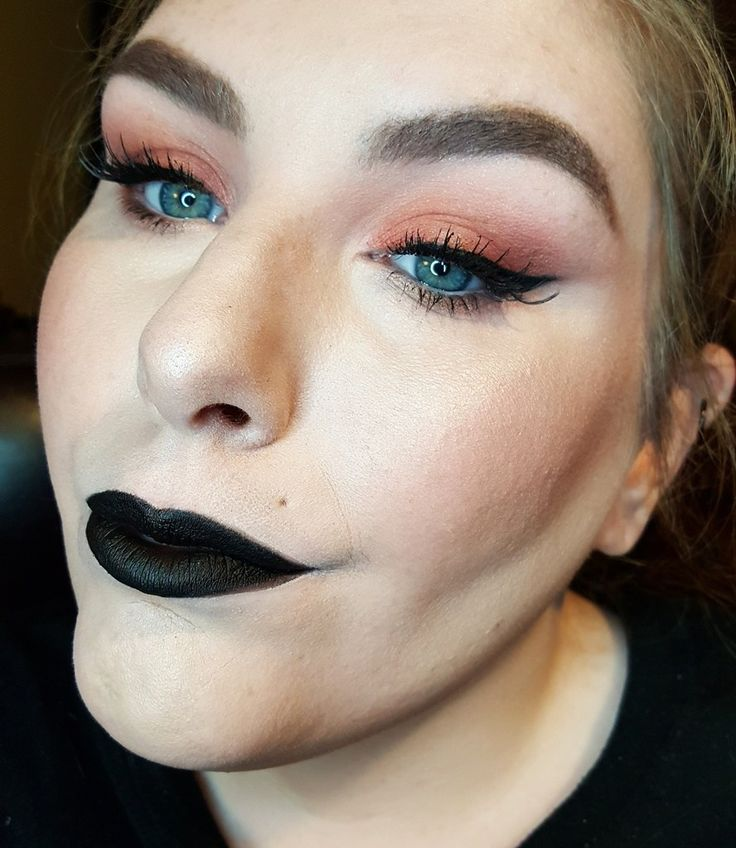 Orange eyeshadow, winged liner, and spidery lashes paired with a matte black lip.
