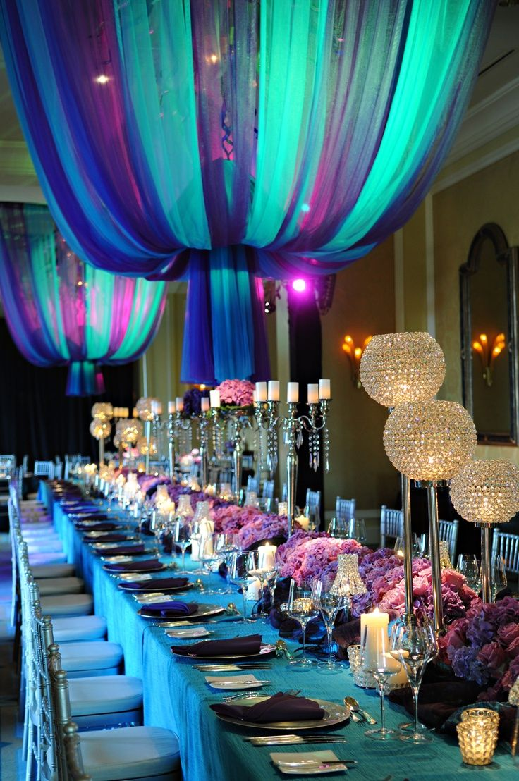 If you do not like the chandeliers at your reception space, maybe fabric instead of floral could be a great way to add huge colour to your space, hide that dated fixture AND look amazing.