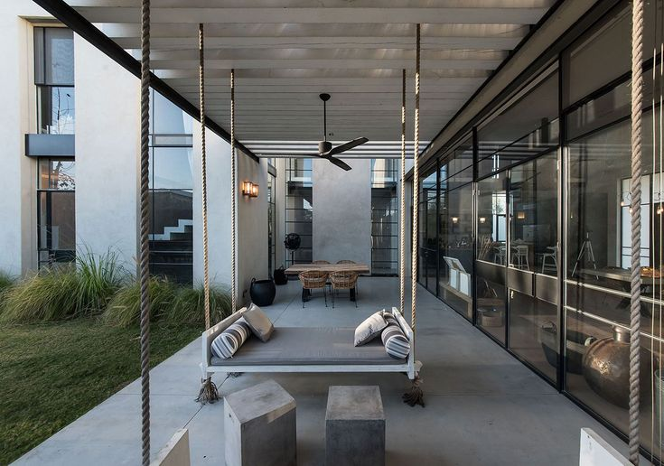 This house designed by Neuman Hayner Architects is composed of two cubes separated by a passage and combining into an L-shaped house. The interiors features several hanged items, like lightings, chairs and beds #swinging #chairs #outdoor