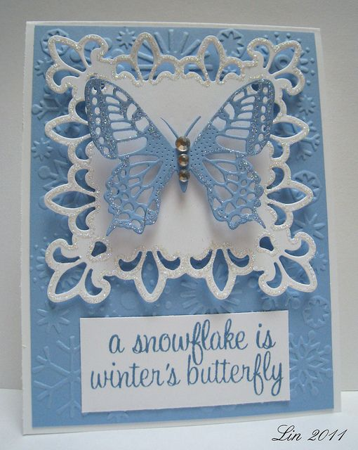 hand crafted winter card ... baby blue and white ... spellbinders fancy die cut with fleur di lis border gently glittered ... die cut lacy butterfly .. snowflakes embossing folder ... delightful sentiment ...
