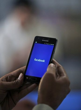 "An Indian man opens a Facebook page on his mobile phone in Hyderabad, India, Thursday, May 17, 2012. The company's shares are expected to begin trading on the Nasdaq Stock Market on Friday under the ticker symbol ""FB"". Facebook is likely to have an estimated market valuation of some $100 billion, making it worth more than Kraft Foods, Ford or Disney. (AP Photo/Mahesh Kumar A.) Photo: Mahesh Kumar A, Associated Press / SF"