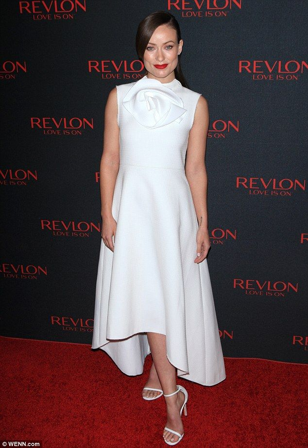 Olivia Wilde wore an elegant white dress featuring a rose detailing around the neckline with matching strappy heels
