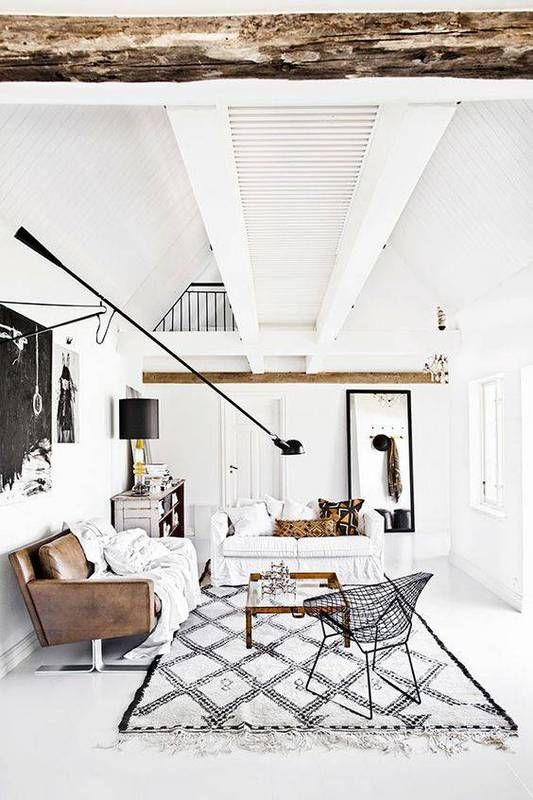 Bright Swedish living space with exposed ceiling beams, a Morrocean area rug, a wire chair, a leather couch, and a moveable sconce