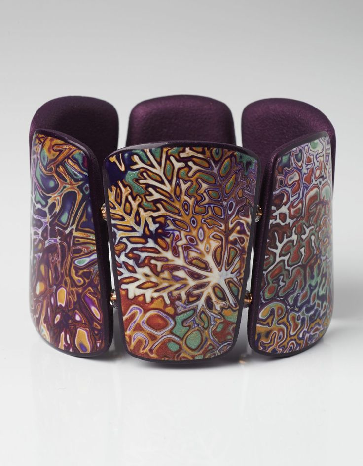 Beautiful example of mokume gane (stack thin sheets of polymer clay in different colors, rubber stamp surface, razor blade away top layers.)