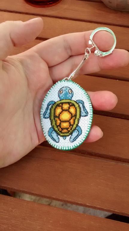 Brelok żółw - handmade, haft krzyżykowy. Haft na kanwie białej, długość 6 cm (bez zapięcia), szerokość 4,5 cm, obrębiony i podszyty zielonym filcem, zapięcie metalowe.