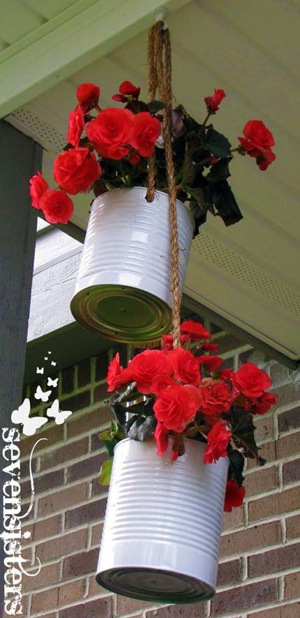 These hanging tin can planters are cute, and if you hang them so they can move like a pulley system, it will make watering each one easier.