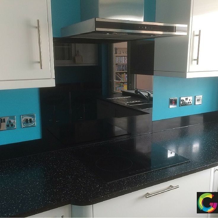 Toughened black cooker splashback with matching upstands to the rest of the kitchen including thin strip under the windowsill.