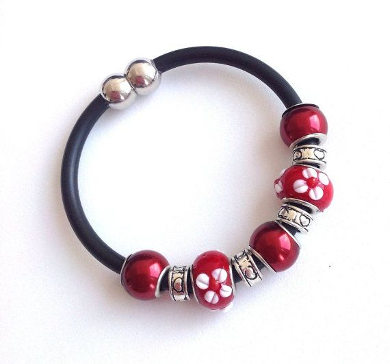 I created this beautiful bracelet using rubber cord, lamp work beads, and cute heart motif spacers. I used a magnetic clasp on this, making it easy to fasten and unfasten. The pictures show the bracelet both fastened and unfastened. This bracelet measures 7 1/2 inches. The flower