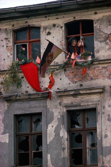 Magnum Photos — Thomas Hoepker — Bautzen, 1974. Dilapidated house in Bautzen during an official festivity. #bunt #farbenfroh #Bautzen #Sachsen #70er #rot #Fenster #Fahne #Flagge #Haus
