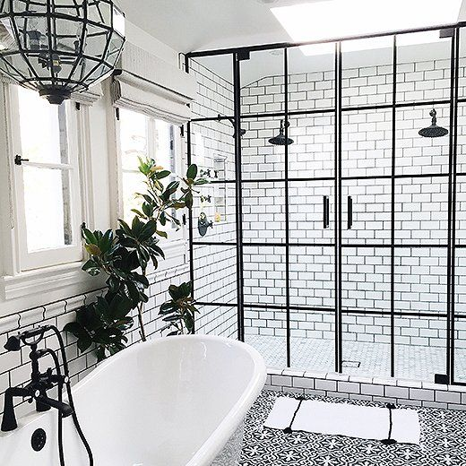 Subway tiles with dark grout and ornate medallion floor tiles set the stage, accentuated by windowpane shower doors with black trim. Captivating geometric lighting and shower and tub fixtures in matte black finishes top off the look.