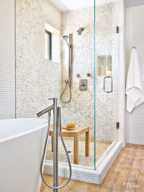 Tile is often used to provide visual direction to a space, but it can also be used to delineate different areas. A warm white color scheme gets a boost with lovely mini subway and pebble tiles.