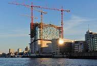 125_4652 | Hamburg am frühen Morgen - die aufgehende Sonne spiegelt sich in einem der modernen Bürogebäude am Kai des Grasbrookhafens. Hohe Baukräne stehen auf der Großbaustelle der Elbphilharmonie. Im Hintergrund die Überseebrücke mit dem Museumsschiff Cap San Diego und die Hochhäuser von Hamburg St. Pauli.