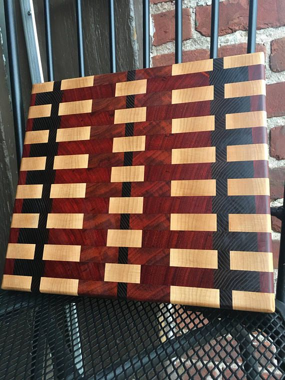 Padauk, Maple, Ash - End Grain Cutting board 11.25 x 12.5 x 1.5 The gorgeous maple floating blocks in the middle of the red are such an eye-catching display its hard to let this one go! You may have seen it unfinished in many of my other pictures and now its up for grabs! There is a twin to this board, it has the same pattern but its the exact opposite. in design. Traditional cutting boards are the staple of EVERY kitchen. Here at Take Root - We take our kitchen time very seriously. We…