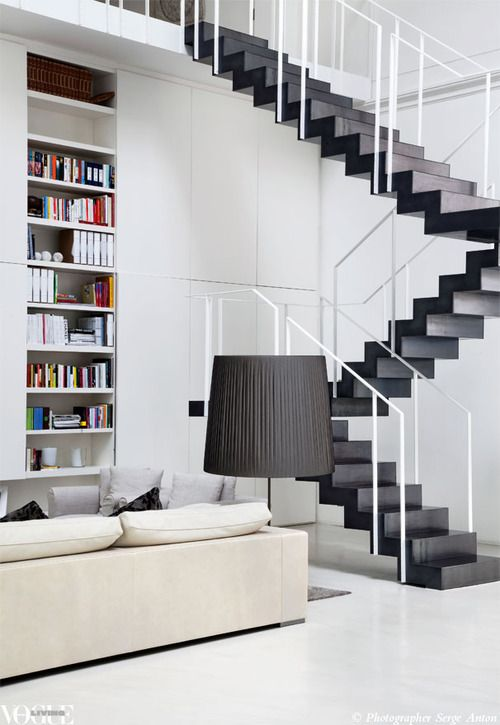 A bookcase neatly slots into a wall beneath the graphic laminated steel staircase by Fratelli Ronchetti in this early 1900s theatre-turned-modern-loft by architect Piero Lissoni.    From 'Home Theatre', a story on page 166 of Vogue Living July/August 2012.    Photograph by Serge Anton