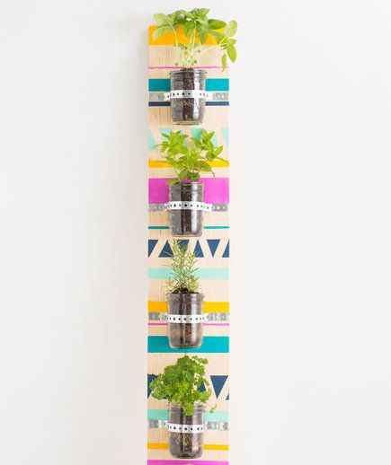 With a long piece of wood, paint, screws, galvanized metal tape, jars, herbs, and potting soil, you can place this hanging herb garden on a kitchen or breakfast nook wall. Create a cool design on the wooden strip with paint and then attach the jars with the galvanized metal tape and screws. Fill the jars with herbs, like in the photo, or succulents or air plants.