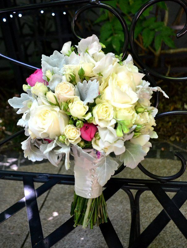 The Brides bouquet has cream and Ivory roses with ivory spray roses and a few pops of bright pink mini David Austin roses, with beautiful silver leaf framing. I do flowers