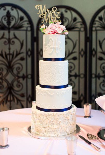 Preppy wedding cake idea - round, four-tiered, fondant-frosted cake with blue ribbon, pink florals and gold laser-cut topper  {Amber Rhodes Photography}