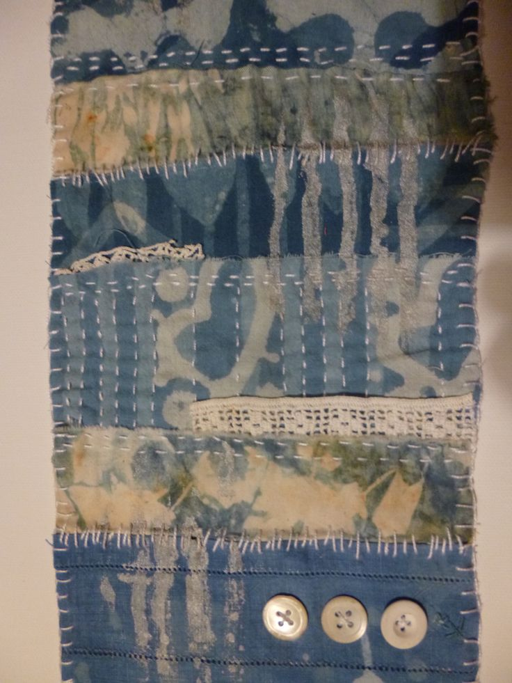 hand stitching on indigo and clay dyed and rusted fabric