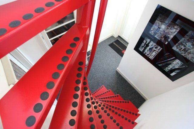 un escalier en colimaçon rouge à pois noirs moderne
