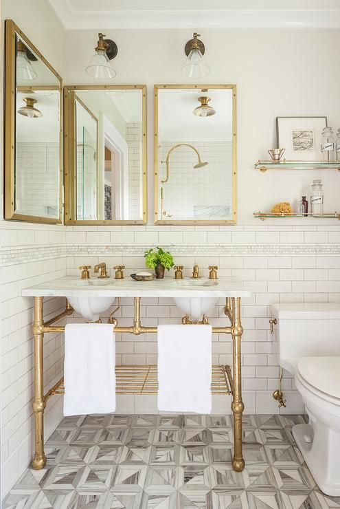 Gorgeous transitional bathroom boasts a stunning white marble and brass double washstand with aged brass faucets and shelf sat under three antiqued brass rivet medicine cabinets from Restoration Hardware and illuminated by two glass and brass downturned sconces.