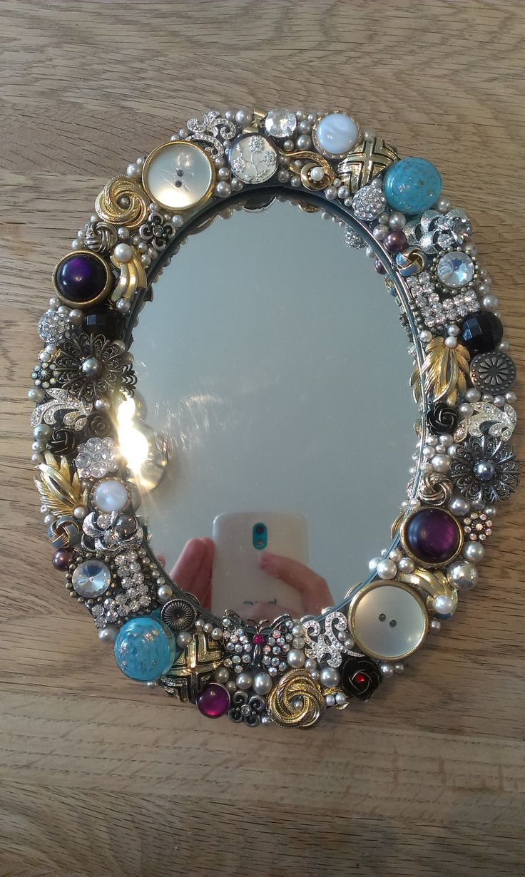 Old clip-on earrings, brooches and buttons from old relatives that I don't use. But they made a pretty mirror! I used silicone to glue them on, and filled every little space with beads from an old necklase. MN