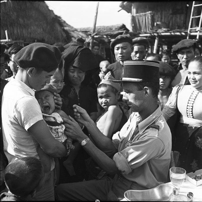 Description : Le médecin-capitaine Le Damany vaccine un nourrisson thaï dans un village de la vallée de Diên Biên Phu. Date : Février 1954