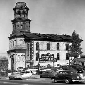 "This October 1955 image shows the old Trinity Methodist Church, which had torn down its steeple months earlier after Hurricane Hazel damaged it beyond repair the year before. Next to the Church Hill building is the used car lot owned by Howard H. Hughes, aka ""Mad Man Dapper Dan,"" who was an eccentric and flamboyant Richmond businessman. In 1965 he had the ""Half Moon"" house built for his family on Cherokee Road overlooking the James River."