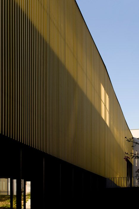 A network of corridors is enclosed behind these slender golden fins in a Lisbon high school.