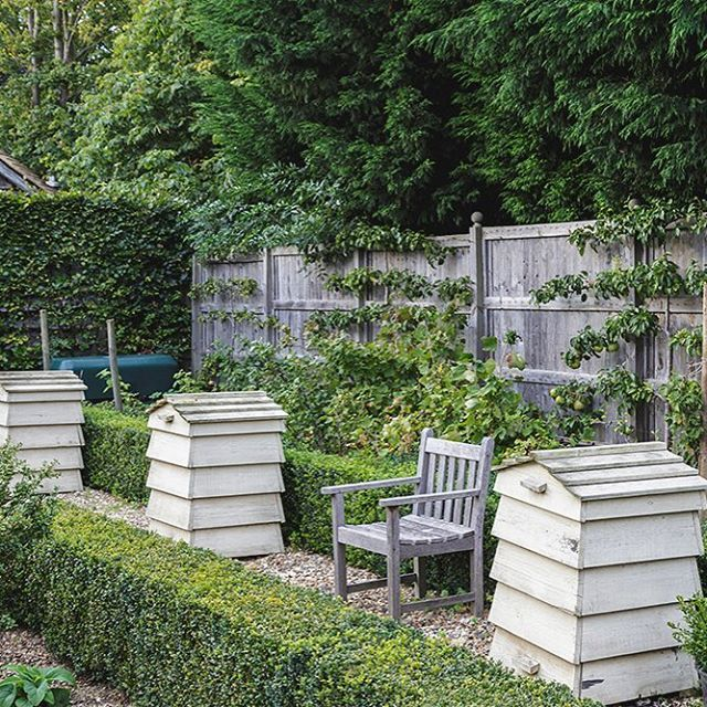 Alex and Graeme Ellisdon's Hertfordshire garden is a swaying mass of tawny grasses, rosy crab apples, rich pink sedum heads and autumn-tinted leaves, where a row of beehives, traditionally kept in kitchen gardens, are used as compost bins. See more in our November issue. #garden #englishgarden #beehive #bench Garden design by Julie Toll, photograph by Mark Bolton.