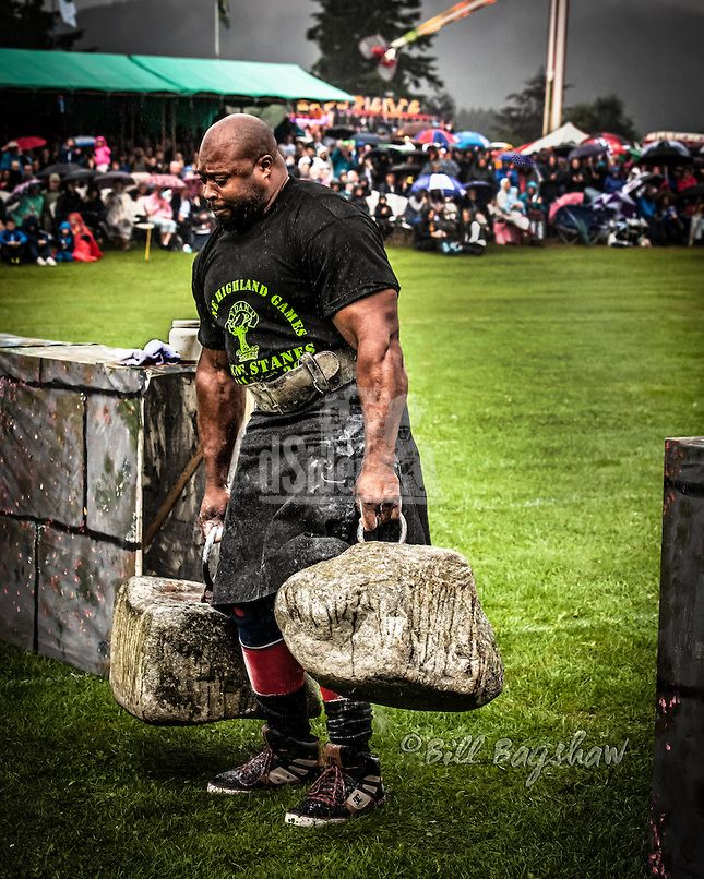Mark Felix one of the worlds strongest men lifts The Dinnie Stanes ( Dinnie Stones ) at Aboyne Highland Games on Royal Deeside