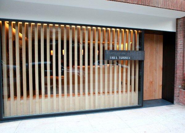 Ir al dentista (casi) no es un trauma en la Ortodoncia Tres Torres, diseñada por el arquitecto Damián Ribas. | diariodesign.com. Label facade wood door.