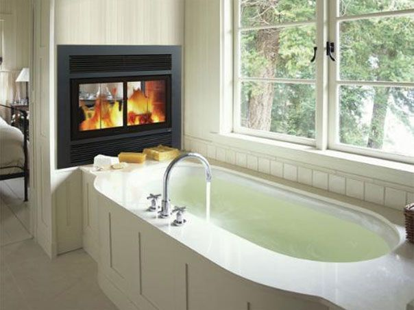 Multi-sided wood burning fireplace is installed in the wall between a bathroom & bedroom.