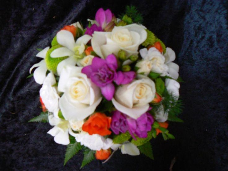 Cream roses, orange & cream spray roses mixed with vibrant pink freesias, green button chrysanthemums, white Dendrobium orchids & white spray carnations