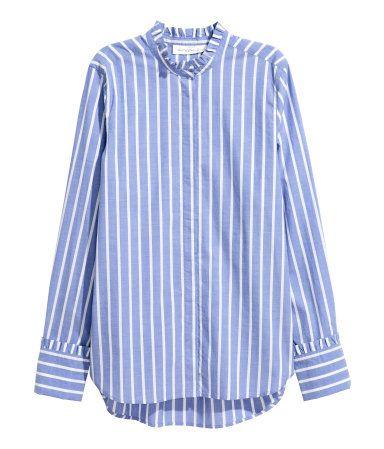 Blauw/gestreept. Een rechte blouse van geweven katoen met een iets langer achterpand. De blouse heeft een halsboordje met een volantrandje, een blinde