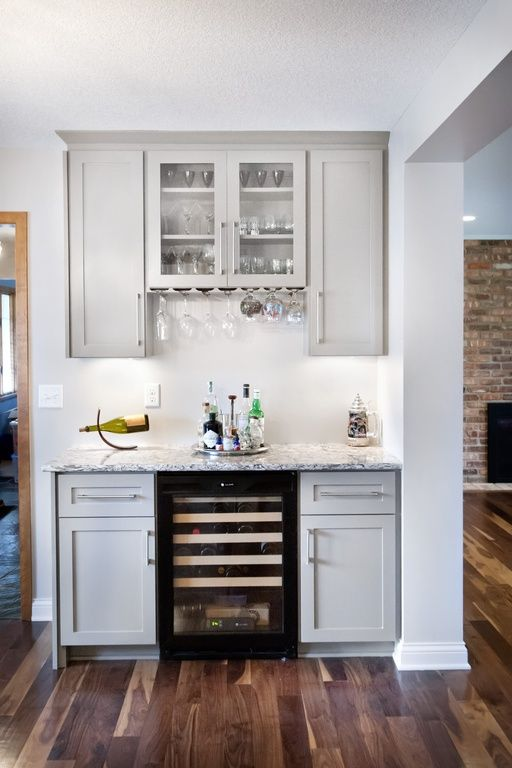 A small white home bar between the kitchen and living room with light gray cabinets and beautiful white granite countertops.