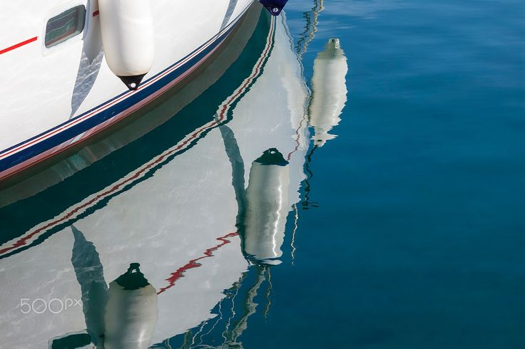 Reflexions of a Sailboat - Sailing boats' reflexions mirroring on the surface of the blue sea.
