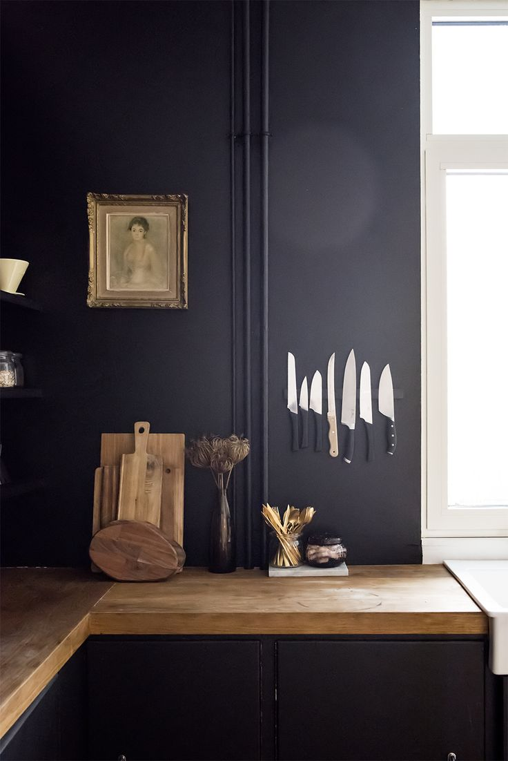 Black kitchen walls with invisible magnetic strip for knives and vintage portrait in a gilt frame on the wall and butcher block countertops.