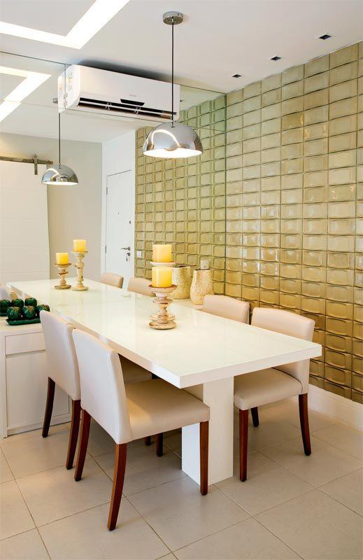 Dicroicas destacam a parede coberta de revestimento cimentício, que dá volume à superfície, dispensando ornamentos. Mesa de laminado e cadeiras revestidas de linho. Projeto das arquitetas Elise e Evelyn Drummond.