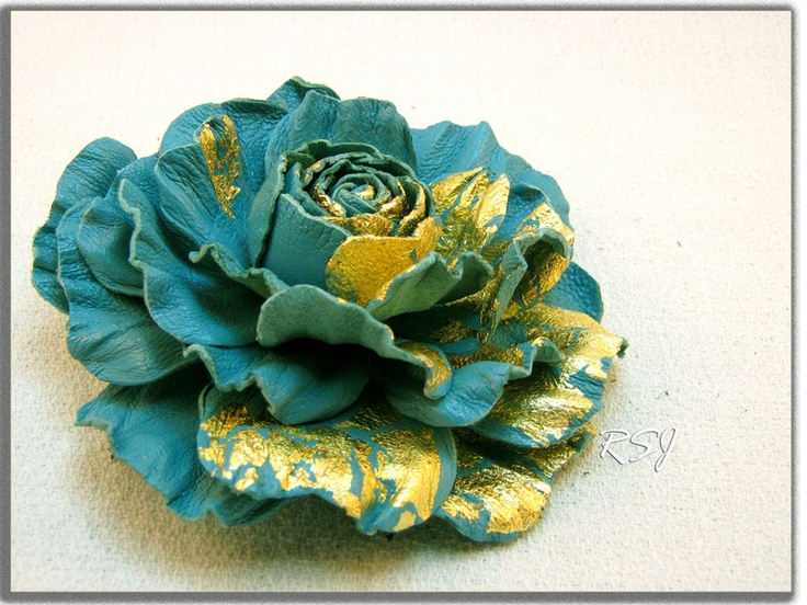 Handcrafted leather brooch and hair clip in turquoise. It has been treated to hold its shape. The flower decorated with a gold leaf technique.