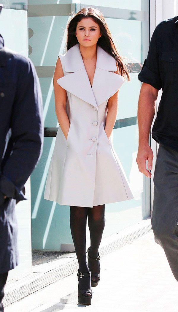 Street style look Selena Gomez com colete cinza fechado, meia calça e sapato preto.