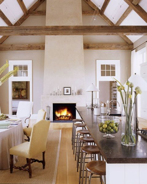 """""""There was a temptation to put a mantelpiece around the fireplace, but it would have been too decorative,"""" says Ina. """"This is a masculine room, and it needs to be very clean."""" Candlesticks on the mantel by Ted Muehling; stools from Robert Stilin; faucet by Waterworks."""