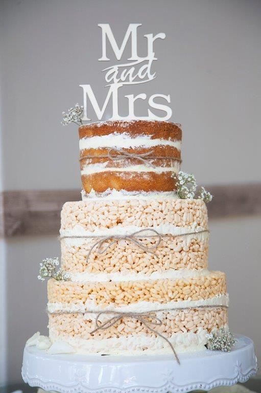 Rice crispy treat naked cake with cake topper. wedding cake