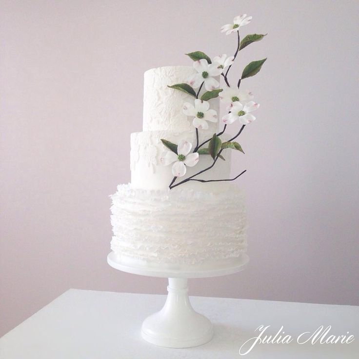 A pretty white lace and ruffled cake, completed with a delicate dogwood blossom branch #weddingcake#whitewedding#dogwood#lace#ruffles#whiteweddingcake#cakelace#sugarflowers#juliamariecakes#cyprus