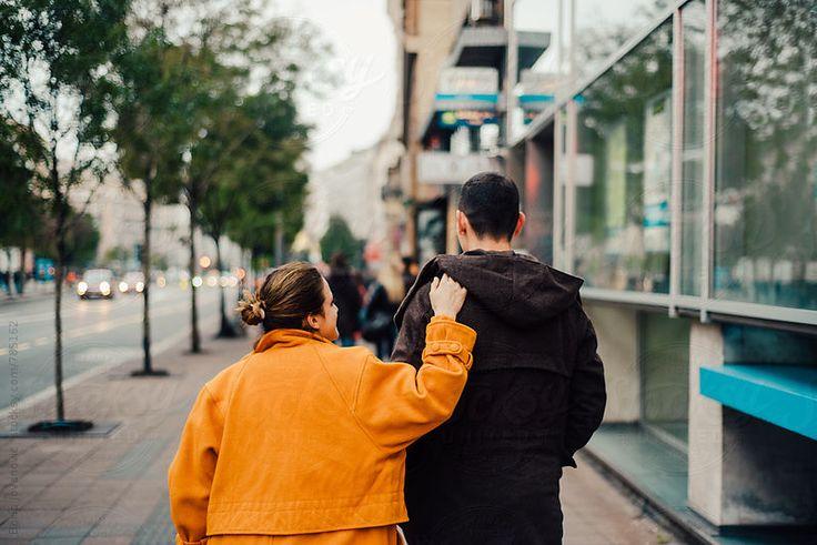 Back shot of two friends walking down the street by Boris Jovanovic